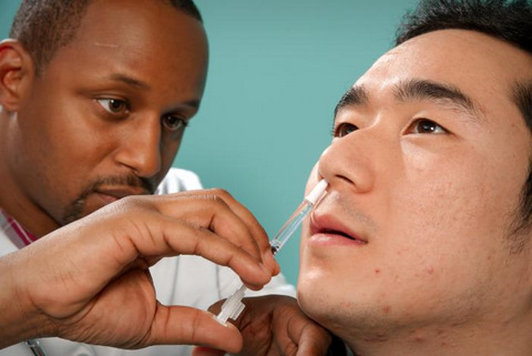 African American Male Nurse Giving a Nasal Spray Vaccinie to Asian American Man