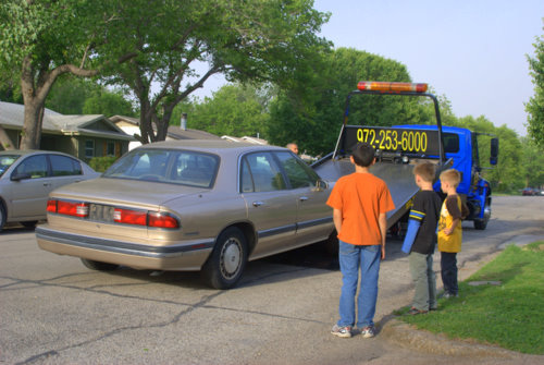 Three Kids Watching a Car Being Towed