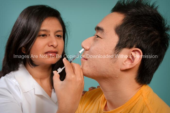 Hispanic Female Nurse Giving Nasal Spray Vaccine to Asian Patient