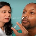 Hispanic Female Nurse Giving Nasal Spray Vaccine to African American Patient