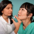 Hispanic Female Nurse Giving Nasal Spray Vaccine to a Patient