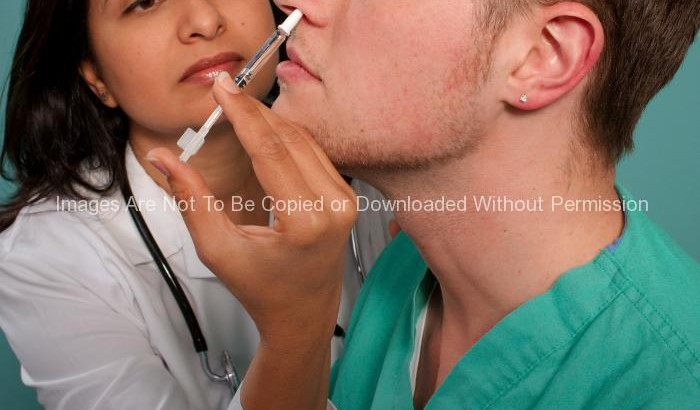Indian Female Nurse Giving Nasal Spray Vaccine to a Patient