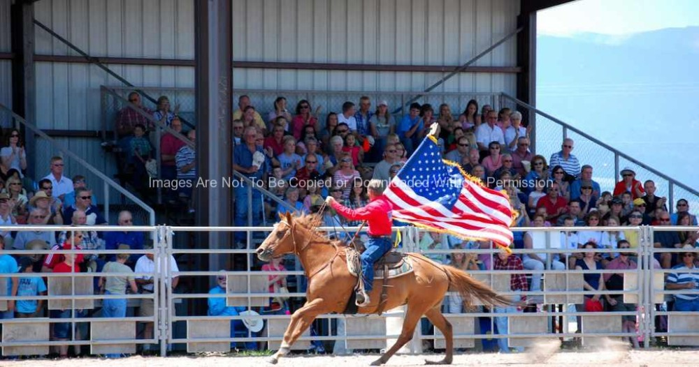 Rodeo cowboy with American flag riding horse