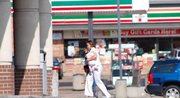 Woman carrying child into a store