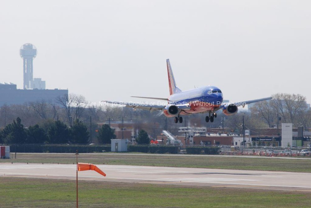 Dallas Texas in Background as Southwest Airlines Jet Lands at Love Field