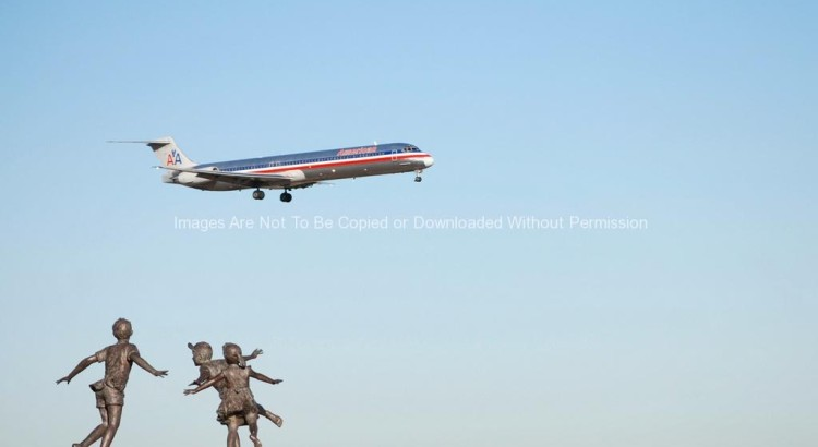 Statue at DFW Airport with Plane Flying Overhead